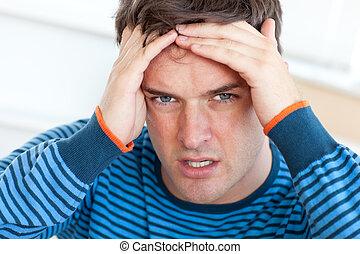 Caucasian man having a headache in the living-room