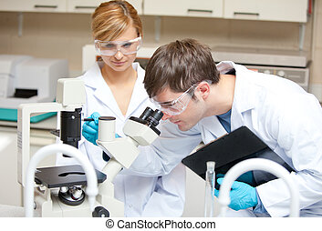 Two scientists observing something with a microscope in...