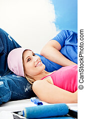 Happy young couple relaxing after painting a room