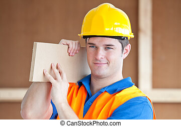 Male worker carrying a wooden board - Young male worker...