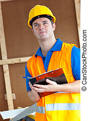 Thoughtful male worker holding a clipboard at work