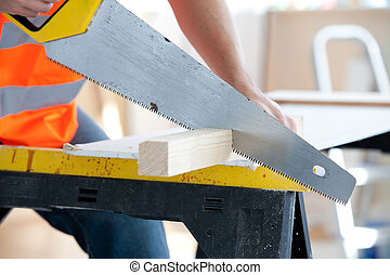 Close-up of a serious male worker sawing a wooden board