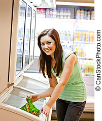 Smiling young woman holding a deep-frozen product in a...