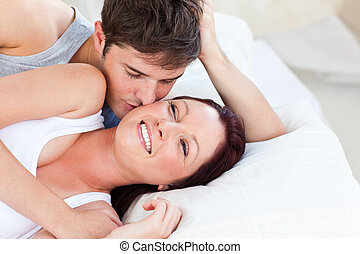 Caring caucasian couple lying on bed in the bedroom at home