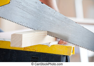 Close-up of a worker sawing a board at work