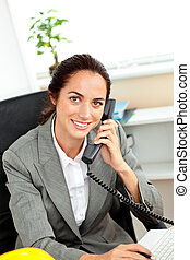 Busy hispanic female architect using her laptop while talking on phone in her office