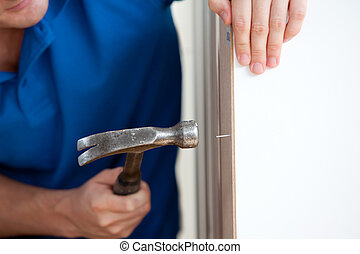 Close-up of a handyman building furniture using a hammer and...