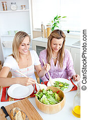 Two glowing female friends eating salad in the kitchen at...