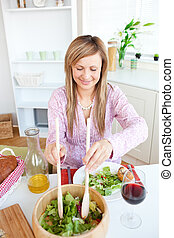 Radiant woman eating salad in the kitchen