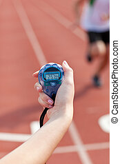 Close-up of a woman holding a chronometer to measure performances of a sprinter in a stadium
