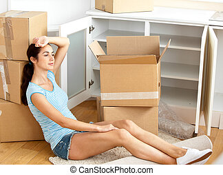Exhausted hispanic young woman sitting on the floor after unpacking boxes in her new house