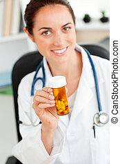 Delighted female doctor holding pills into the camera in her...