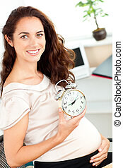 Radiant pregnant businesswoman holding an alarm clock and sitting at her desk in her office