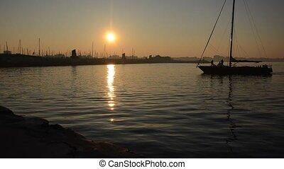 Sailboat back to the marina at sunset