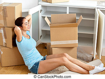 Relaxing woman with unpacking boxes - Relaxing hispanic...