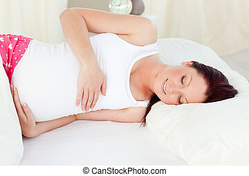 Smiling pregnant woman resting in her bed in the bedroom at...