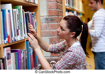 Pretty young woman looking for a book in a bookstore