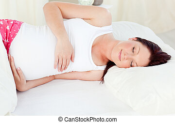Radiant pregnant woman sleeping in her bed at home