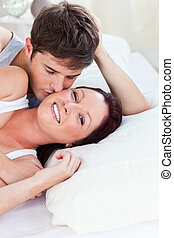 Loving caucasian couple lying on bed in the bedroom at home
