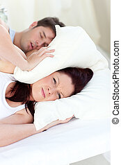 Young woman annoyed by the snores of her boyfriend in the...