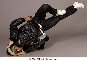 Portrait of hip hop dancer in head stand on grey background