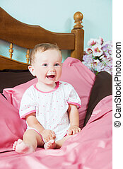 Cute happy laughing baby playing on bed.