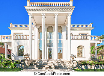 The facade of a luxurious residence with columns in the...