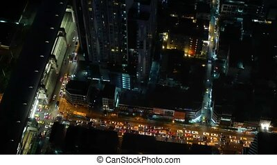Aerial night vertical view of skyscraper rooftops and...
