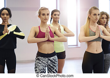 Group of young women taking exercise class in gym