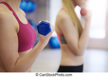 Women training with dumbells in the gym