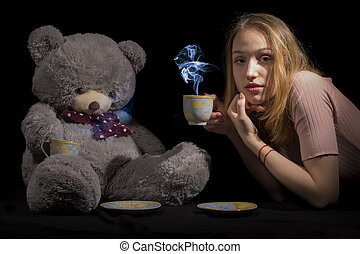 Girl and teddy - Tea time for young girl with big teddy on...