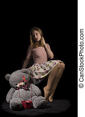 Girl and teddy - Young girl with big teddy on black...