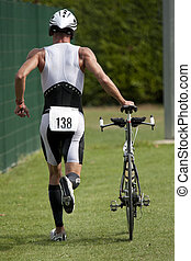 Triathlete pushing his bike in the transition zone