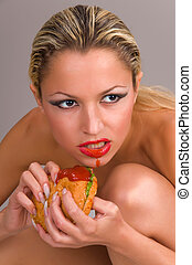 beautiful naked woman eating a hamburger