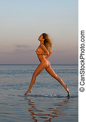 naked woman running on the beach