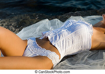 woman lying on a rock in a corset