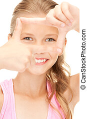 pretty girl creating a frame with fingers - picture of...