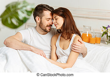 Young adult heterosexual couple lying on bed in bedroom at...