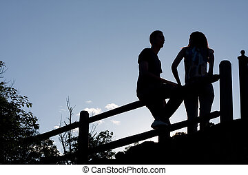 Couple Silhouette - Silhouette of a young couple hanging out...