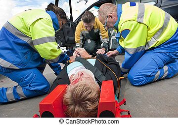 First Aid - Paramedics and a fireman strapping a wounded...