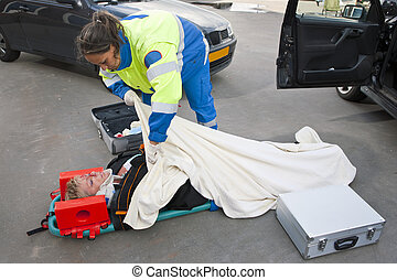 Injured woman - Female paramedic putting a blanket over an...