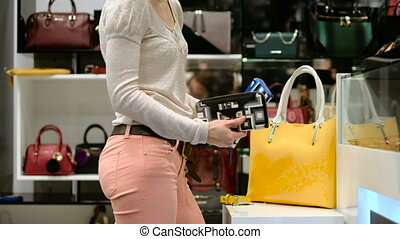 A beautiful girl picks a bag. bag shop Fashion store -...