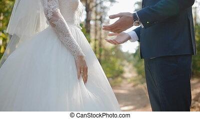 Groom kiss hands of his bride. Posing outdoor. Closeup. Slow...