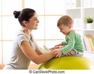 Happy mother with baby doing gymnastics on the big fitness ball in the gym