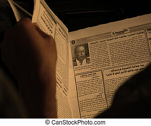 Reading a newspaper in arabic writing, in ocher tones,...