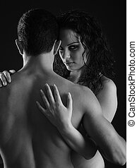 Passionate woman - woman hugging man isolated on black...