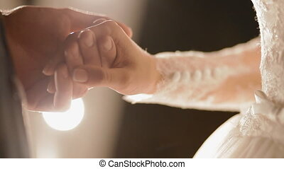 Groom hold the hands of his bride in front of the lights