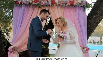 Putting wedding ring on finger - Bride and groom exchange...