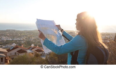 Traveler girl searching right direction on map - Back side...