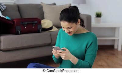 woman with smartphone at home going to travel - tourism,...
